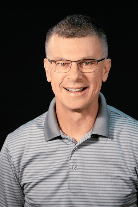Steve Webb headshot - man wearing glasses and collared shirt smiling for camera.